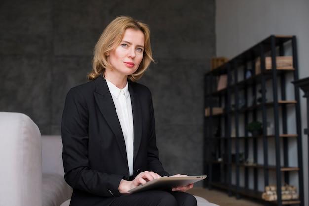 Mulher de negócios loiro pensativo sentado com tablet Foto gratuita