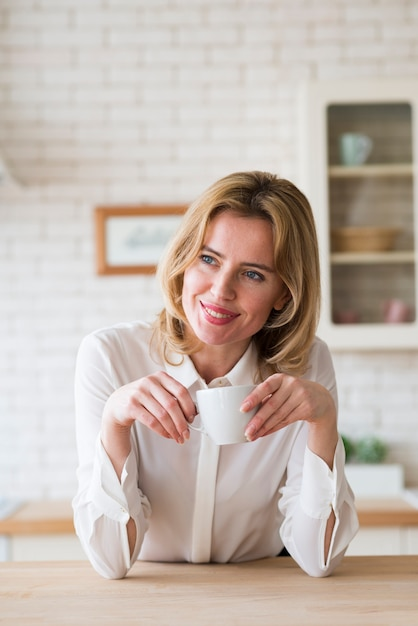 Mulher de negócios loiro sentado com uma xícara de café Foto gratuita