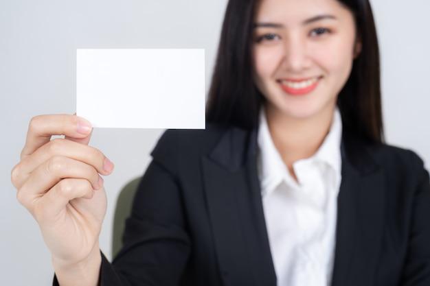 Mulher de negócios, mantendo e mostrando o cartão vazio ou cartão de nome Foto gratuita