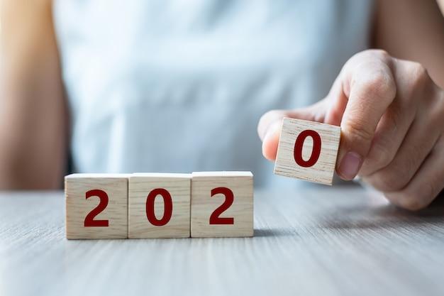 Mulher de negócios, mantendo o cubo de madeira com a palavra 2020 Foto Premium