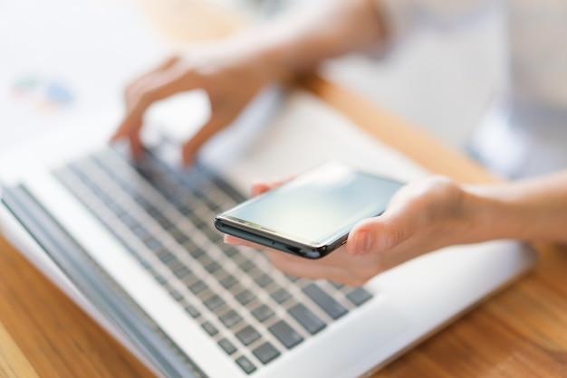 Mulher de negócios mão com gráficos financeiros e telefone celular sobre o laptop na mesa. Foto gratuita