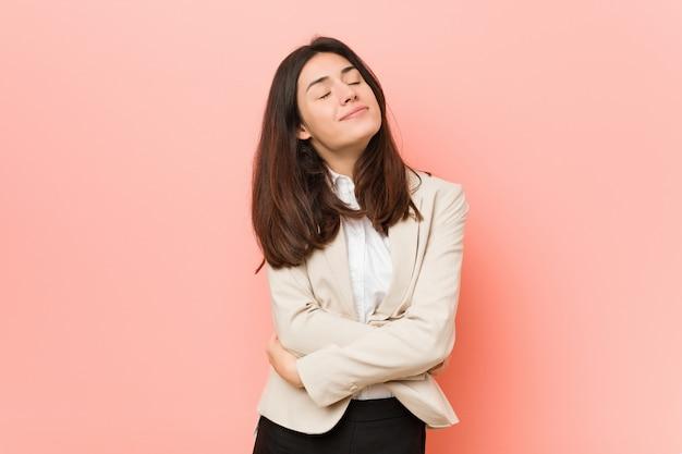 Mulher de negócios morena jovem contra uma parede rosa abraços, sorrindo despreocupado e feliz. Foto Premium