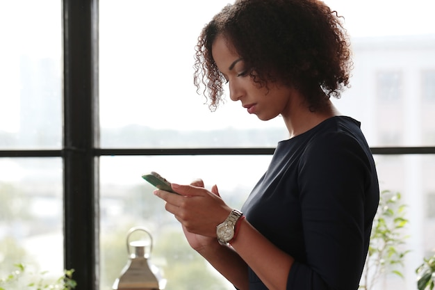 Mulher de negócios negra em um vestido preto rígido checando seus e-mails ao telefone Foto gratuita