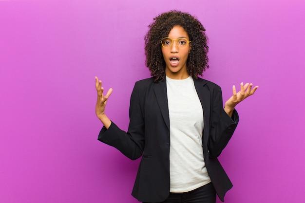 Mulher de negócios negra jovem se sentindo extremamente chocada e surpresa, ansiosa e em pânico, com um olhar estressado e horrorizado Foto Premium