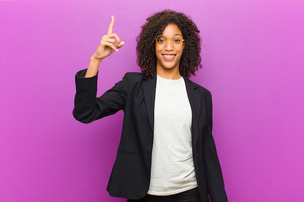 Mulher de negócios negra jovem se sentindo um gênio feliz e animado depois de realizar uma idéia, alegremente levantando o dedo, eureka! Foto Premium
