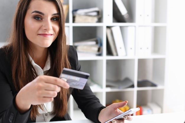 Mulher de negócios no escritório tem um cartão de crédito plástico na mão Foto Premium