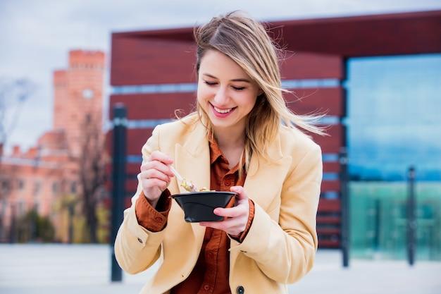 Mulher de negócios nova com salada na cidade urbana ao ar livre. Foto Premium