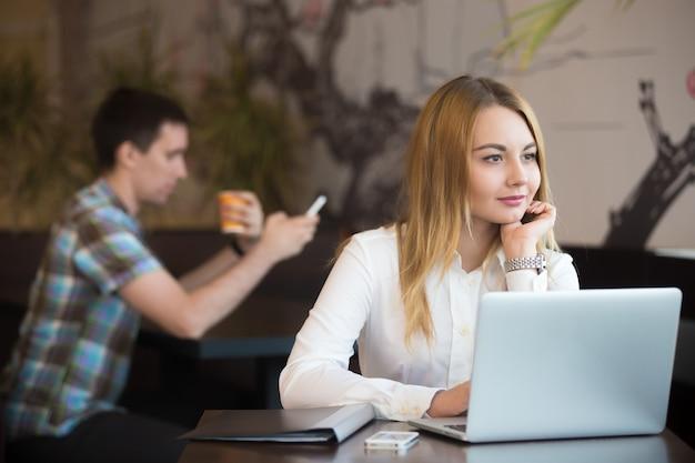 Mulher de negócios pensativa trabalhando no café Foto gratuita