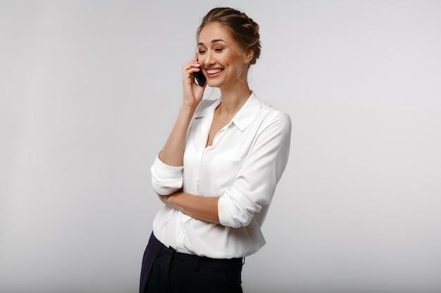 Mulher de negócios positiva afável alegre com um telefone celular. conversação. retrato de negócios Foto Premium