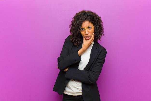 Mulher de negócios preto jovem com a boca e os olhos bem abertos e mão no queixo, sentindo-se desagradavelmente chocado, dizendo o que ou uau Foto Premium
