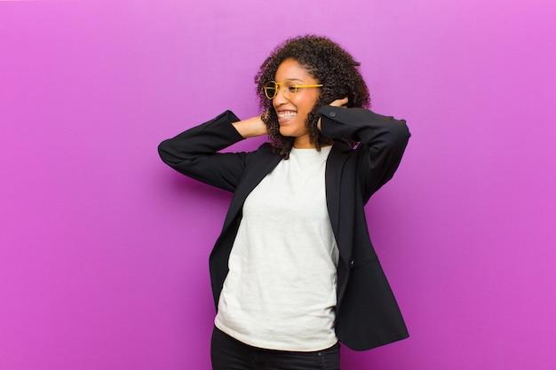 Mulher de negócios preto jovem se sentindo feliz, animado e surpreso, olhando para o lado com as duas mãos no rosto Foto Premium