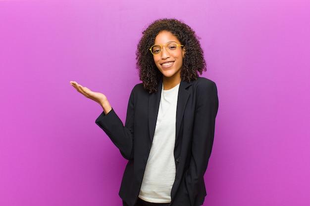 Mulher de negócios preto jovem se sentindo feliz, surpreso e alegre, sorrindo com atitude positiva, percebendo uma solução ou idéia Foto Premium