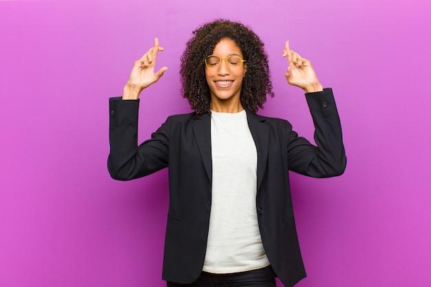 Mulher de negócios preto jovem sentindo nervoso e esperançoso, cruzando os dedos, rezando e esperando por boa sorte Foto Premium