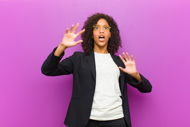 Mulher de negócios preto jovem sentindo-se estupefato e assustado, temendo algo assustador, com as mãos abertas na frente dizendo ficar longe Foto Premium