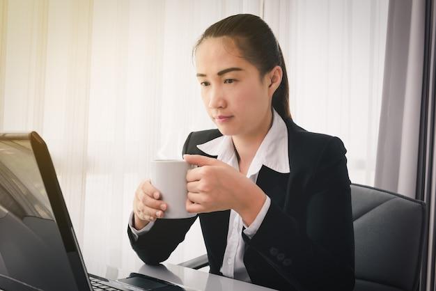 Mulher de negócios que bebe o café / chá e que usa o computador labtop no escritório. hora de relaxar conceitos Foto Premium
