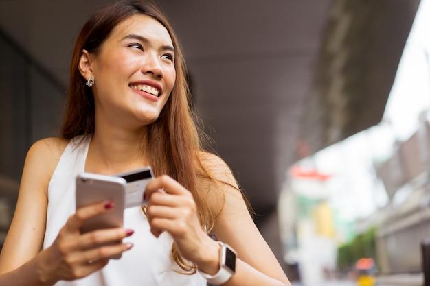 Mulher de negócios, segurando o smartphone com cartão de crédito para pagar compras on-line e-commerce Foto Premium