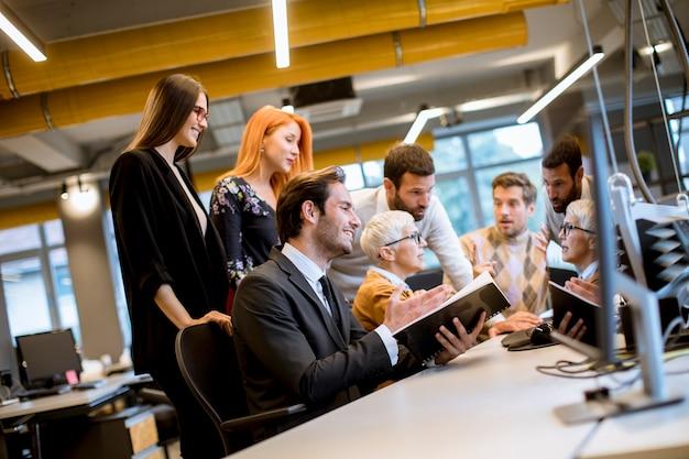 Mulher de negócios sênior trabalhando em conjunto com jovens empresários no escritório Foto Premium