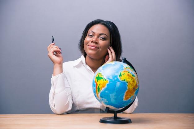 Mulher de negócios sentada à mesa com caneta e globo Foto Premium