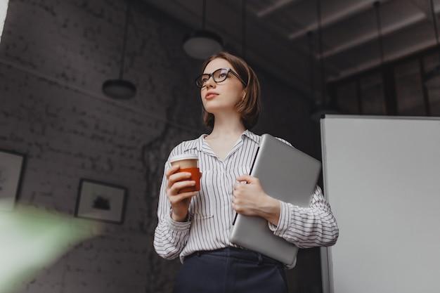 Mulher de negócios sérios em uma blusa elegante e calça preta, segurando o laptop e bebendo café no escritório. Foto gratuita