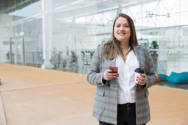 Mulher de negócios sonhador, segurando o smartphone e beber ao ar livre Foto gratuita