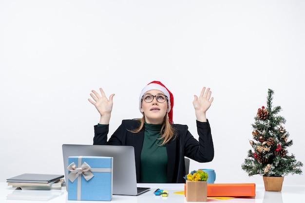 Mulher de negócios surpresa com chapéu de papai noel, sentada à mesa com uma árvore de natal e um presente apontando para cima, sobre fundo branco Foto gratuita