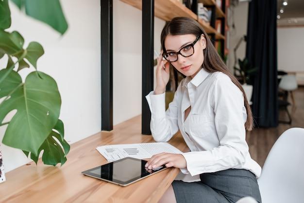 Mulher de negócios trabalha no escritório com tablet e documentos com gráficos Foto Premium