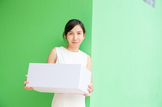 Mulher de negócios, trabalhando com compras on-line de caixa de parcela sobre fundo verde pastel. Foto Premium