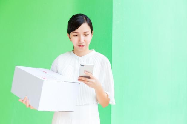 Mulher de negócios, trabalhando com telefone celular e encomendas de compras on-line caixa sobre fundo verde pastel. Foto Premium