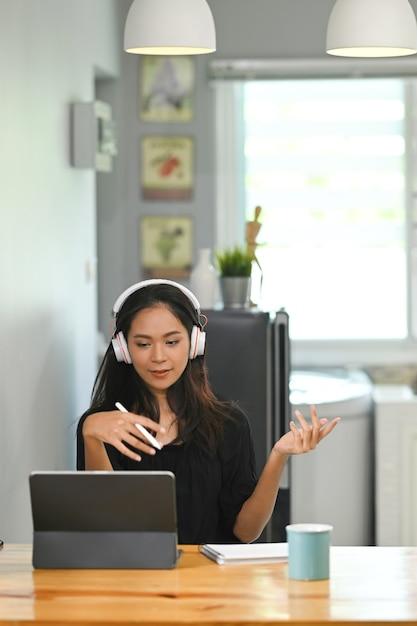 Mulher de negócios, trabalhando em tablet digital em casa, durante a videoconferência com um grupo de parceiros de negócios. Foto Premium