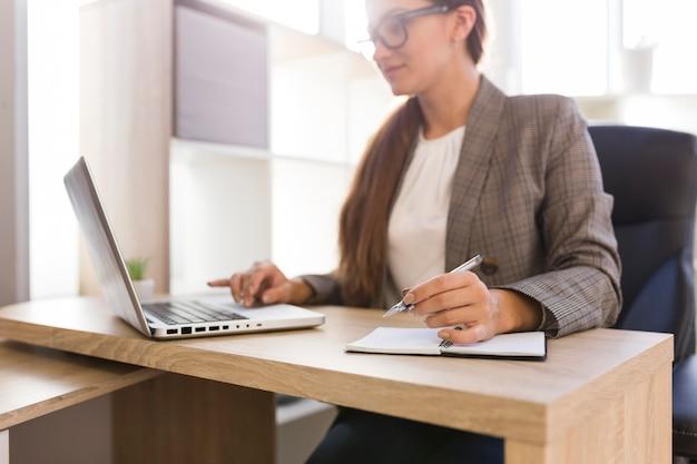 Mulher de negócios trabalhando em um laptop em seu escritório Foto gratuita