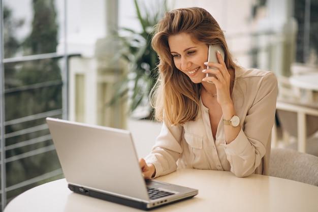 Mulher de negócios, trabalhando no laptop e falando ao telefone Foto gratuita