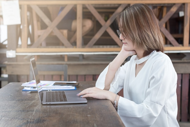 Mulher de negócios usando pelo computador ou laptop trabalhando no café do escritório. Foto Premium