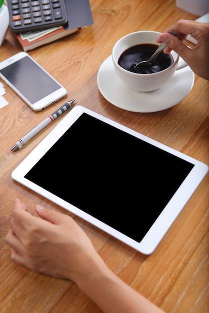 Mulher de negócios usando tablet maquete com café preto e artigos de papelaria de escritório na mesa de madeira Foto Premium