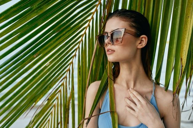 Mulher de óculos em um fundo de palmeiras Foto Premium