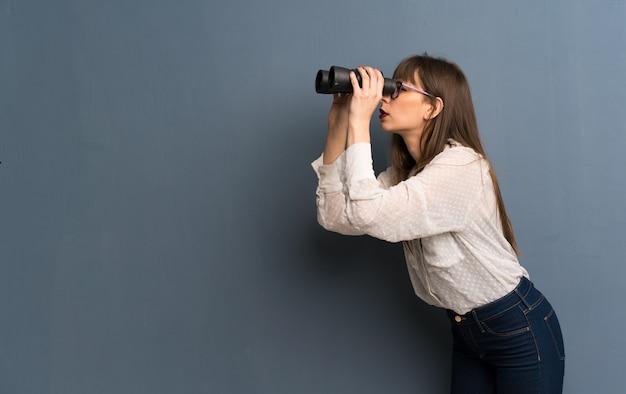 Mulher de óculos parede azul e olhando à distância com binóculos Foto Premium