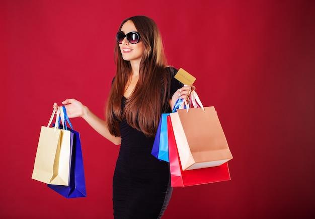 Mulher de óculos segurando sacolas de compras Foto Premium