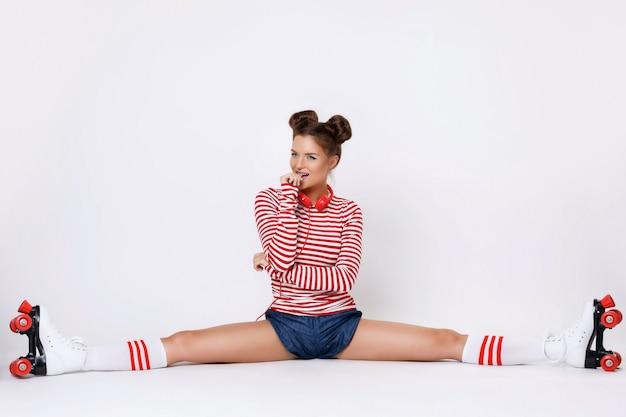 Mulher de patins sentado na divisão Foto Premium