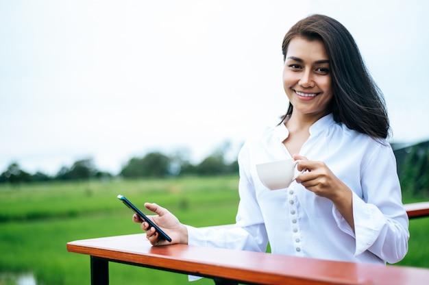 Mulher de pé em um smartphone e segurando uma xícara de café Foto gratuita