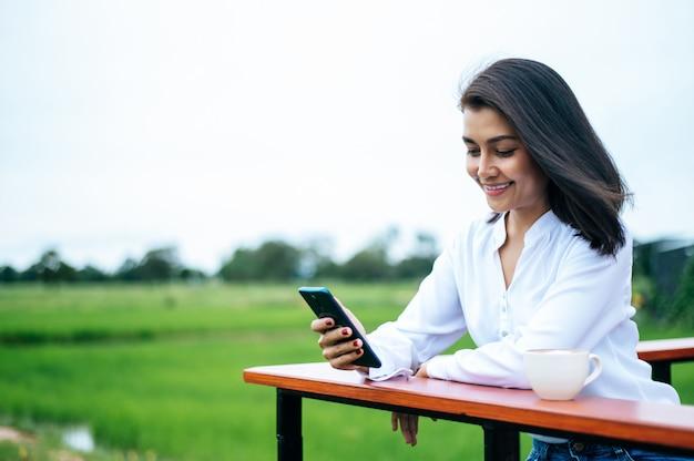 Mulher de pé em um smartphone e tomar uma xícara de café Foto gratuita