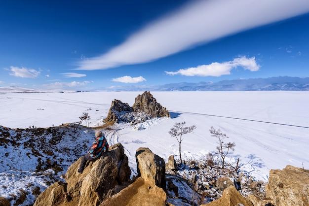 Mulher de pé em uma pedra na rocha shamanka em olkhon Foto Premium