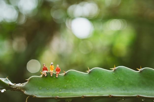 Mulher de pessoas em miniatura, sentado na natureza verde, folha de palmeira de açúcar Foto Premium