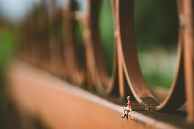 Mulher de pessoas em miniatura, sentado na parede Foto Premium