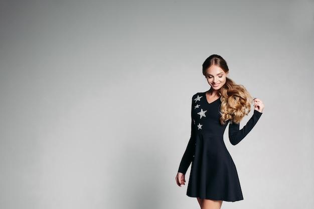 Mulher de positividade no elegante vestido preto com estrelas dançando. Foto Premium