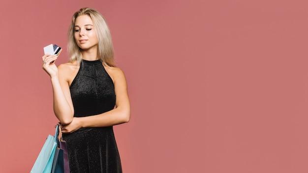 Mulher de preto com cartões de crédito e sacolas de compras Foto gratuita