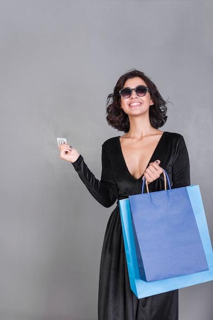 Mulher de preto com sacolas brilhantes e cartão de crédito Foto gratuita