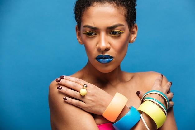 Mulher de raça mista tensa ou decepcionada colorida com maquiagem da moda e acessórios posando com as mãos cruzadas no peito, parede azul Foto gratuita