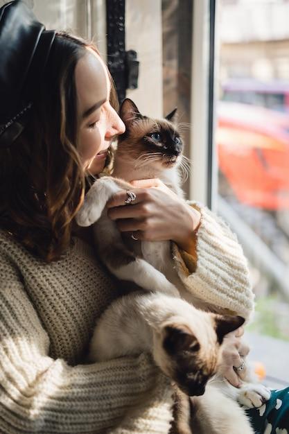 Mulher de retrato com gatos siameses Foto gratuita