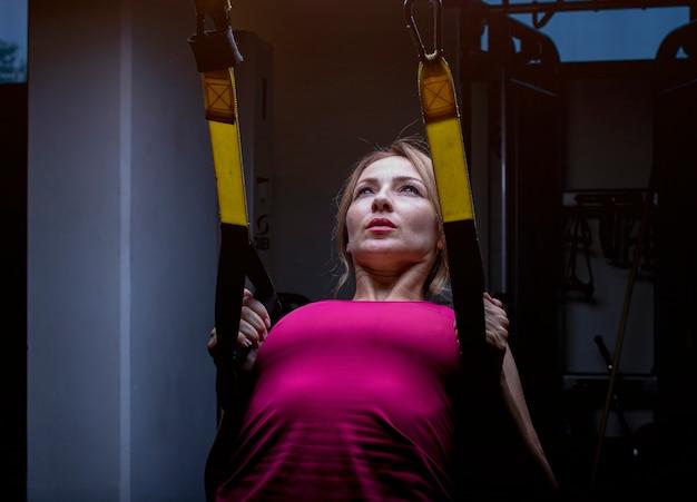Mulher de rosa, fazendo o treinamento traseiro com a máquina de extensão traseira em um ginásio. Foto gratuita