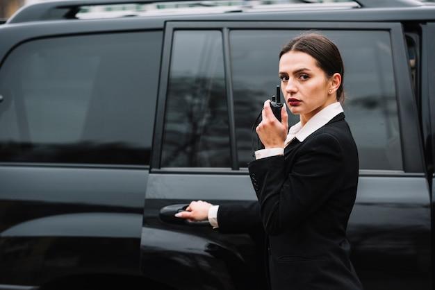 Mulher de segurança na frente do carro Foto gratuita