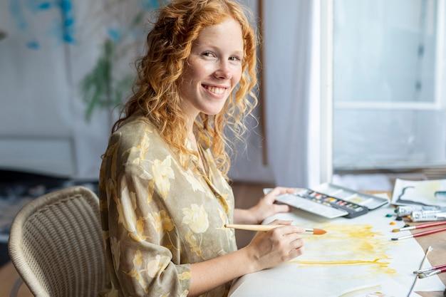 Mulher de smiley pintura dentro de casa Foto gratuita